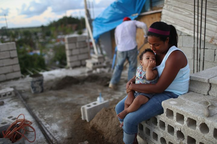 A young woman with her 9-month-old baby after their home in Puerto Rico was destroyed by Hurricane Maria,...