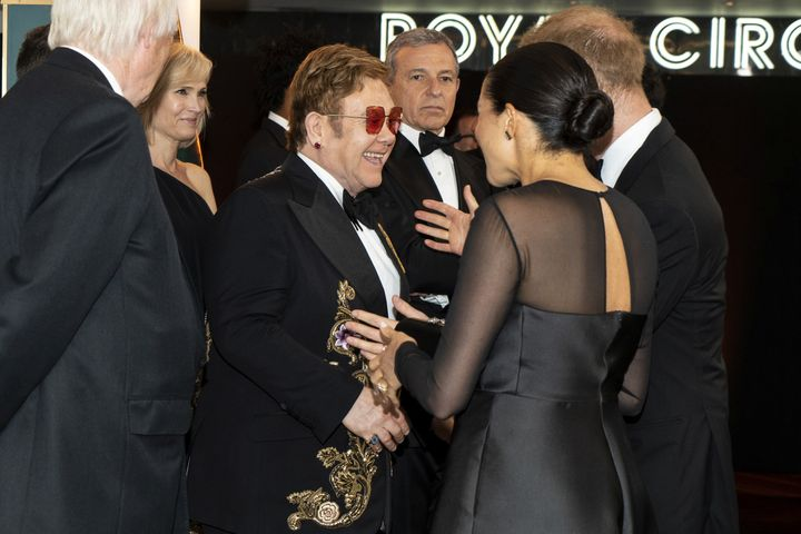 Harry and Meghan chat with Elton John as they arrive for the European premiere of