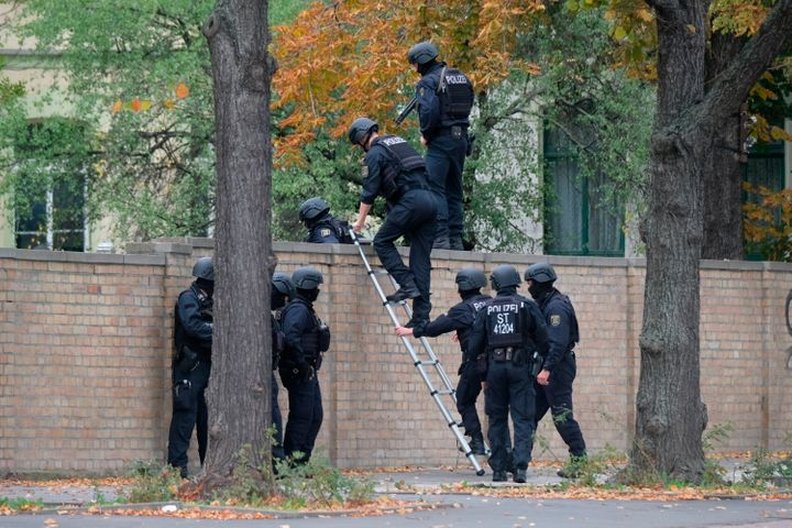 Police officers cross a wall at a crime scene in Halle, Germany, Wednesday, Oct. 9,