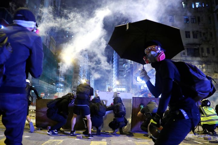 Protesters take cover behind boards during a protest in the Mong Kok area in Hong Kong, China November 11, 2019. (REUTERS/Tho