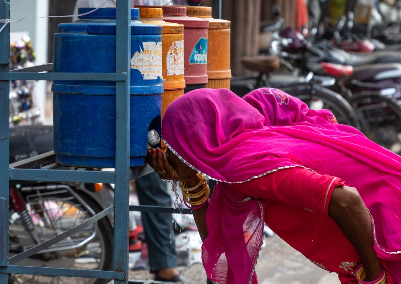 Women drinking water in the street during the heat wave in Bikaner, Rajasthan, India on July 25, 2019....