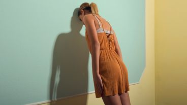 Rear View Of Sad Woman Leaning On Wall