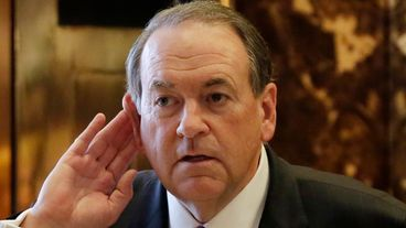 Former Arkansas Gov. Mike Huckabee cups his ear to hear a reporter's question as he waits for the elevator at Trump Tower in New York, Friday, Nov. 18, 2016. (AP Photo/Richard Drew)